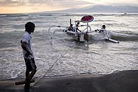 Local men secure their wooden boat agaisnt the increasing waves and tide in Gili Air, Gili Islands, Indonesia.