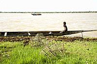 Segou (Mali). Pinnace (traditional wooden boat) in the river Niger with little boy in it. Fish traps in foreground.