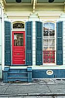 New Orleans, LA, French Quarter. Close Up of Entry Door and Shuttered Window on a Small, Pastel Painted Home.