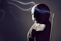 Praying Buddha statue with burning incense smoke in dramatic dim light on dark gray background.