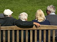 Two couples sitting in park bench, England