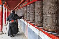 Tibetan people spinning the prayer wheels around Mani Temple (Mani Shicheng) a famous landmark in the Tibetan city of Yushu (Jyekundo), Qinghai, China...