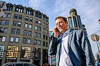 Close up look of a middle age businessman standing in front of the office building while talking on his phone.