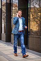 A middle age businessman walking next to the office building while talking on his phone.