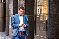 A middle age businessman walking next to the office building while using his smartphone.