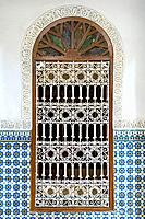 Morocco, Marrakech-Safi (Marrakesh-Tensift-El Haouz) region, Marrakesh. Ornate window surrounded by colorful wall tiles at the Heritage Museum, housed...