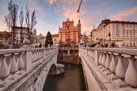 Franciscan Church of the Annunciation and the Triple Bridge over the Ljubljanica River, with Christmas decorations, Ljubljana, Slovenia.