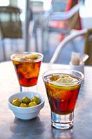 Spanish aperitif: two glasses of red vermouth with green olives in a terrace. Madrid, Spain.