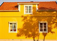 Shadow of tree on yellow painted timber house, Sweden, Scandinavia.