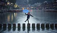 Happy girl in the ancient town, Fenghuang, Hunan Province, China.
