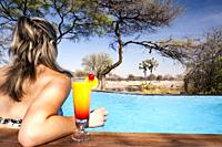 Young woman with drink in swimming pool at Onguma Tented Camp, Onguma Game Reserve, Namibia, Africa.