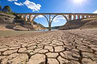 landscape of dry earth ground and viaduct, extreme drought in Entrepenas reservoir, in Guadalajara, Castilla, Spain Europe.