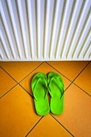 green slippers on a tiled bathroom floor with a radiator on the wall , Stuttgart , Germany.