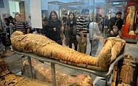 Visitors look at Egyptian mummies in British Museum, London, UK.