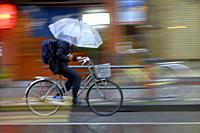 Man riding a bicycle with holding an umbrella,Tokyo,Japan,Asia.