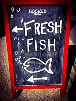 A handwritten sign on a chalkboard for a fish monger selling fresh fish, Halifax, Canada.