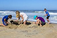 Avon, Outer Banks, North Carolina, USA. Children Making a Sand Castle on the Beach.