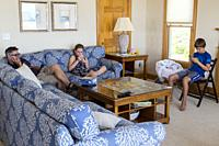 Avon, Outer Banks, North Carolina, USA. Typical American Family Using Cell Phones and Mobile gaming Devices in the Living Room While at a Beach vacati...