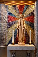 Carved wood statue of Mary Mother of God with 12 star crown standing on moon and serpent at side altar with candles and sunburst mosaic Toronto Ontari...