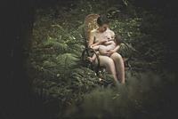 Mother and baby at the time of breastfeeding in the middle of a forest. Maternity in its purest state. Ties between mother and daughter.