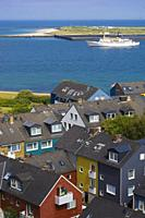 Helgoland Germany colorful houses in town seen from the plateau of the main island toward the island Düne / Dune with ship
