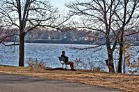 A young man is resting on a bench in an autumn park, Neshaminy State Park, Bucks County, Pennsylvania, USA.