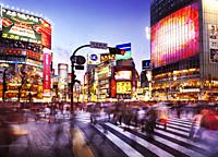 Crowd of people crossing Meiji dori street at Shibuya station busy intersection lit with colorful signs and ads in the evening rush hour. Shibuya, Tok...