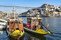 traditional Rabelo boats for Port wine now used for cruises. On the River Douro waterfront in the Ribeira district of Porto, Portugal. with the Dom Lu...
