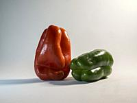Red and green peppers on white background.