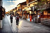 Cyclists on an empty Hanamikoji Dori street in Gion district in morning sunrise before all the shops and restaurants start opening. Hanami-koji, Gionm...