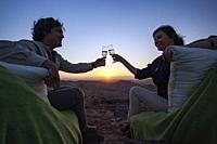 Sunset toast overlooking vast red rock landscape of Damaraland - Huab Under Canvas, Damaraland, Namibia, Africa.