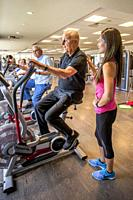 Accompanied by his Asian American instructor, a healthy 92-year-old man works out on an exercise bicycle in the gymnasium of a senior center in Huntin...