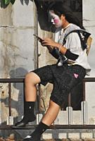 Itoman, Okinawa, Japan: girl with Smartphone at the O-tsunahiki Festival