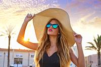 Blond teen girl sunglasses and pamela sun hat at palm tree sunset.