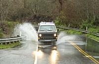 USA, California, Petaluma. 1984 Volkswagen Westfalia van driving through deep puddle on highway. Southern California during heavy rains in the winter.