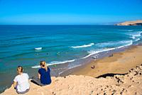 Two girls watching wave surfers at Paradise beach, Maroc
