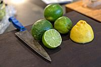 Lemons and Limes, Two Cut in Half, on a Cutting Board, Knife on the Side. NYC.