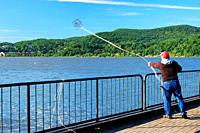 A man casts his crab trap from a dock in Cold Spring, New York.