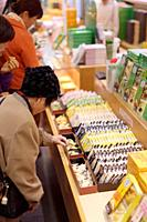 People sampling Japanese sweets, Yatsuhashi triangles at a souvenir confectionery store in Kyoto, Japan.