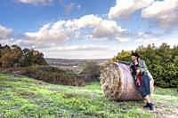Front view of woman leaning on hay bale at field against dramatic sky. Bonarcado, Sardinia. Italy.