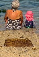 Granny. A grandmother and her little grand daughter sit in the sand at the edge of a tidal pool. Cape Town, South Africa.
