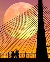 Silhouettes of people at sunset, walking near the Zakim Bridge in Boston, Massachusetts, as the full moon rises