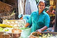 Balinese woman laughing whilst she works in a produce market in Ubud, Bali, Indonesia.