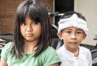 Balinese girl and boy watching a procession in Ubud, the island´s cultural capital. The boy wears traditional costume. Bali, Indonesia.