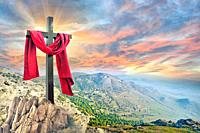 cross with red cloth against the dramatic sky.