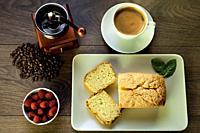 sponge cake, raspberries, cup of coffee, coffee beans and coffee grinder on wood.