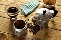Italian coffee maker, napkin, brown sugar bowl, cup of coffee and coffee beans on wood table.