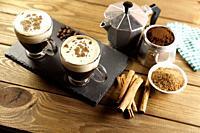 two cup of coffee, Italian coffee maker, coffee beans, cinnamon, napkin and brown sugar bowl on wood table.