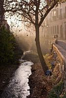 View along the Carrera del Darro river in afternoon sunhaze in December in Granada, Andalucia, Spain.