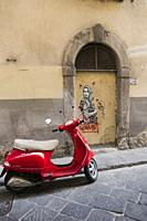 Bright red scooter parked in front of a black and white graffiti image of a young woman surrounded by red hearts, hugging her arms and gazing past the...